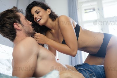 Young couple being intimate in bedroom. Sensual lovers making love in bedroom
