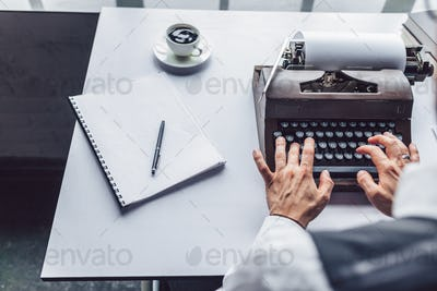 Male hands typing on a typewriter