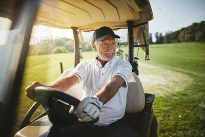 Senior man driving his golf cart on a fairway