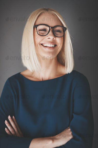 Smiling businesswoman standing with arms crossed against a gray background