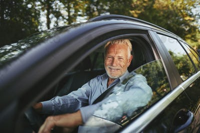 Smiling senior man driving along a road in the countryside