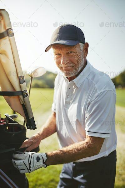 Smiling senior man looking through his golf club bag