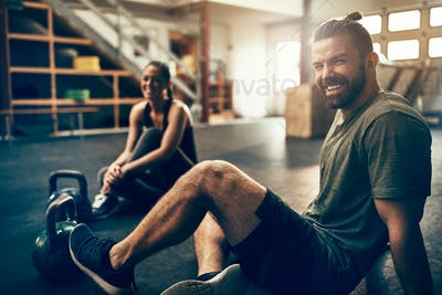 Smiling young people sitting in a gym after working out