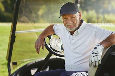 Senior man smiling while sitting in a golf cart
