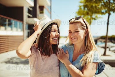 Two laughing young girlfriends walking together in the city