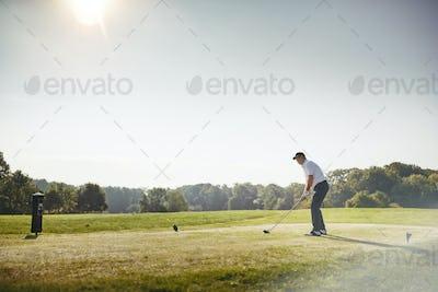 Senior man preparing to drive his ball while playing golf