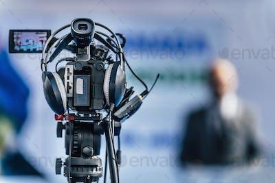 Media Event. Camera Recording. Male Speaker On Stage