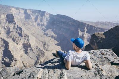 Tourist resting on the edge of cliff