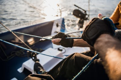 Close-up of male hands in gloves pulling rope of sailboat while mooring yacht and sitting with