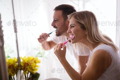 Couple washing teeth in morning