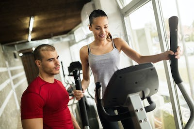 Personal trainer and student in gym