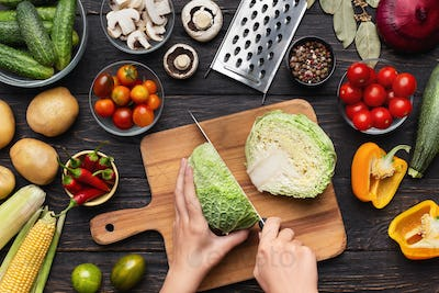 Female hands chopping savoy cabbage on wooden board