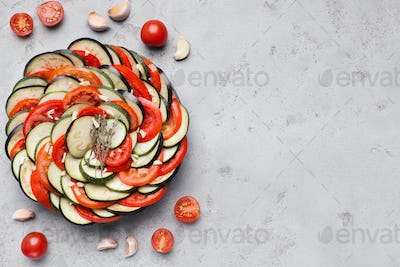 Vegetable ratatouille on gray table background, top view