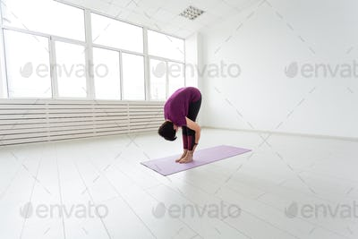 People, sport, yoga and healthcare concept - Side view of a woman doing stretching leaning down
