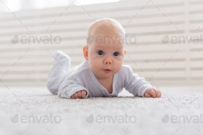 Childhood, infant and people concept - small baby lying on the floor