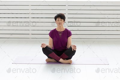 Yoga, harmony, people concept - Middle aged woman sitting in lotus position with closed eyes