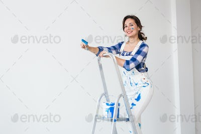 Repair, renovation and people concept - Happy young woman paint wall at home with copy space