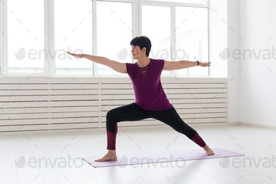 People, yoga, sport and healthcare concept - Middle-aged woman standing in Warrior over white