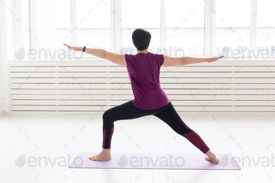 People, sport and healthcare concept - Middle-aged woman practicing yoga, standing in Warrior two