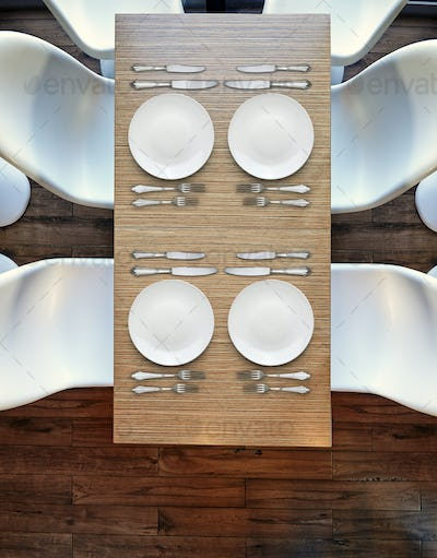 Top view from above on four empty plates on wooden table.