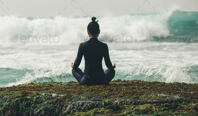 Yoga woman meditation at the seaside cliff edge facing the coming strong sea waves