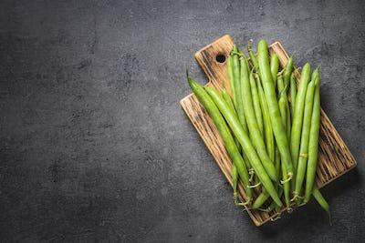 Green beans on black slate background