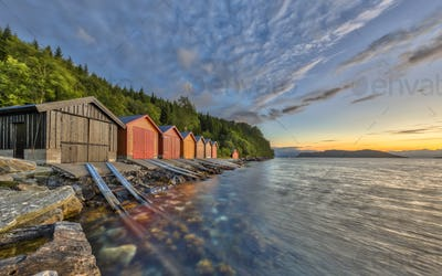 Sunset over Norwegian fjord with Colorful Boathouses