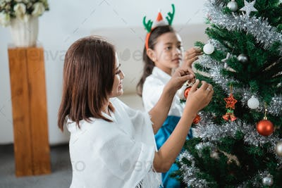 mom and daughter decorating christmas tree