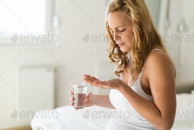 Pregnant woman taking pill