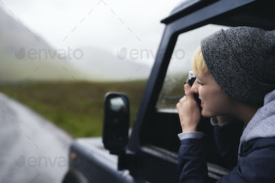 Woman taking a photo out of the car window