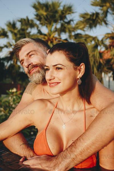 Honeymooners in a swimming pool at a resort