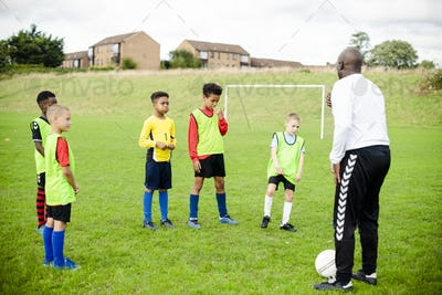 Football coach training his junior players