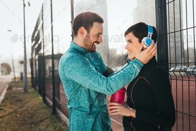 Beautiful couple flirting outdoor before exercising and jogging
