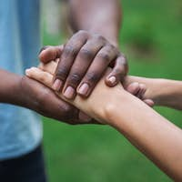 Black caregiver supporting woman hand in park