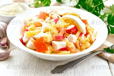 Salad of surimi and tomatoes with eggs on light board