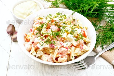 Salad of surimi and eggs with mayonnaise on light board