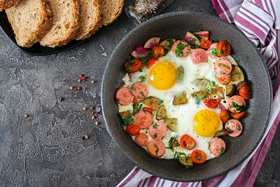 Frying pan with tasty cooked egg, sausages and vegetables on grey table. Breakfast. Top view