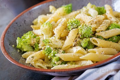 Penne pasta with cabbage romanesco on black table. Vegetarian food. Italian menu