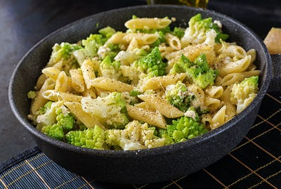Penne pasta with cabbage romanesco on black table. Vegetarian food. Italian menu.