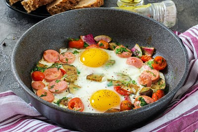 Frying pan with tasty cooked egg, sausages and vegetables on grey table. Breakfast.