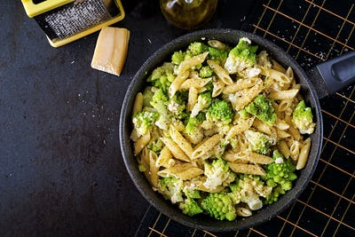 Penne pasta with cabbage romanesco on black table. Vegetarian food. Italian menu. Top view. Flat lay