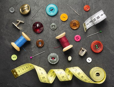 sewing tools and accessories on slate stone