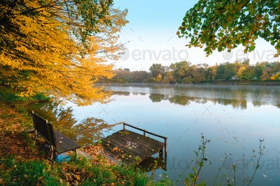 Autumn foliage lake in morning with pier