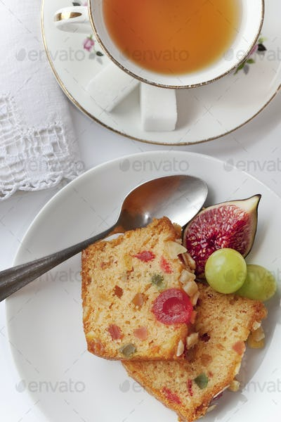 Fruits cake and tea cup on a table