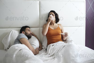 Young Woman Sneezing For Cold In Bed With Man
