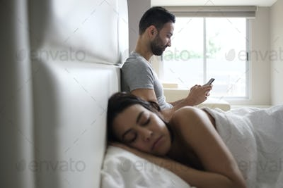 Couple In Bed With Cheating Man Texting On Smartphone