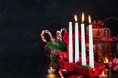 Four Christmas Advent candles and holiday decorations around on
