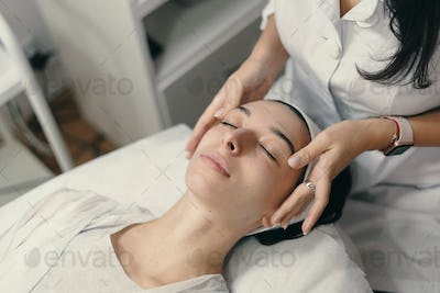 Young woman lies with closed eyes, cosmetologist making procedur