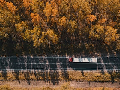 Aerial view of truck on road through forest in autumn