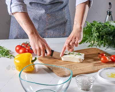 Woman's hands cut the cheese with the sprouts on the wooden board on the kitchen table with